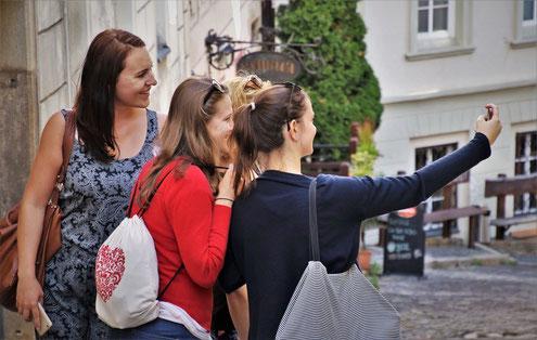 Eine Gruppe junger Frauen, die Spaße haben und Fotos machen, stehen in einer Gasse in der Altstadt von Wien.