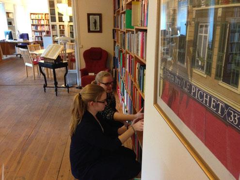 Maria Korten und Stephanie Jarvers sortieren Bücher in der Bibliothek des Newman-Institutes