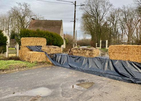 Ballots de paille à l'entrée du village pour éviter les débordements par la route. Le ru passe sous les ballots tandis que l'excès d'eau est dirigé dans une pâture.