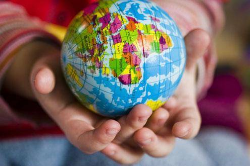 Kinderhände halten den Globus