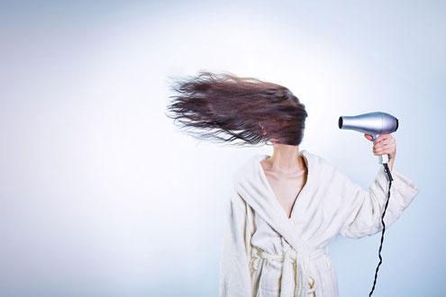 Junge Frau föhnt sich die Haare
