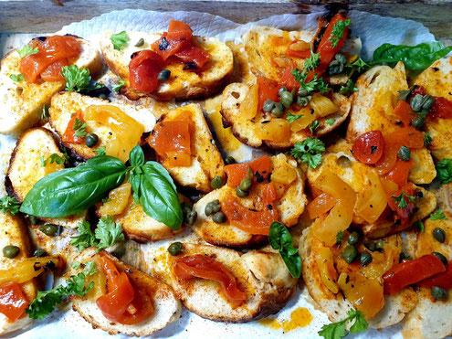 Griechische Bruschetta: Baguettebrotscheiben mit Paprika, Olivenöl und Weissweinessig belegt.