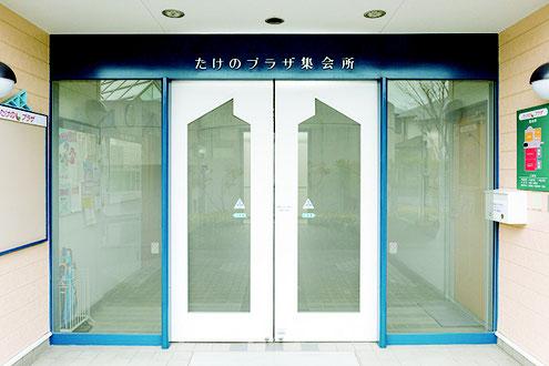 たけのパーク(集会所)入り口写真、右にポストと見取り図、中央は白い自動ドア、左には掲示板がある