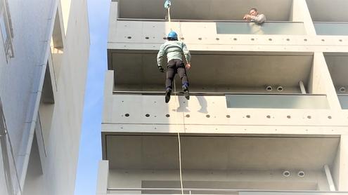 緩降機の降下試験をする消防設備士