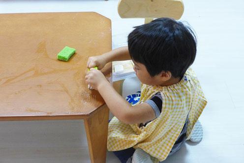 フィオーレコース(2歳児)のお友だちがモンテッソーリ活動で日常生活の練習として、机磨きに取り組んでいます。