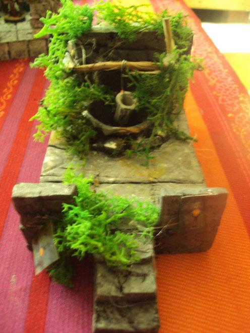 Le puit... Le seau est constiué d'une mèche (à brico)  coupée et peinte Quelques brindilles et un pot de petit suisse créent  le puit .