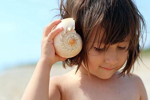 Systemische Hörtherapie | Kind mit Muschel am Ohr