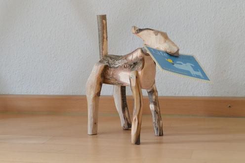 Eine Hundeskultpur, etwa 20cm hoch, gefertigt aus grob bearbeiteten Aststücken, die als Rumpf, Beine, Rute und Kopf miteinander verschraubt sind. In das Maul kann Post gesteckt werden.