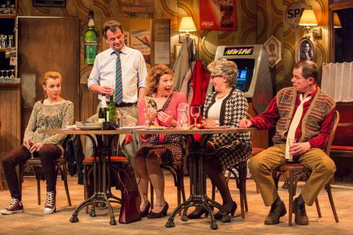 Les acteurs de la pièce sur scène dans le décor d'un café.
