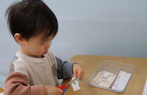 1歳児がモンテッソーリの個別活動ではさみのお仕事に挑戦しています。