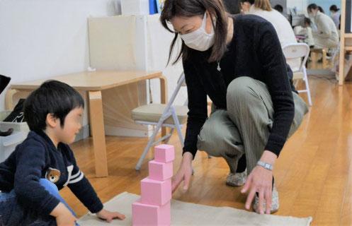 1歳児がモンテッソーリの個別活動でピンクタワーを順番に積み上げています。