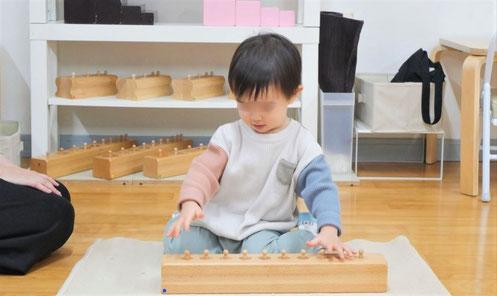 1歳児がモンテッソーリの個別活動ではめ込み円柱の活動に集中して取り組んでいます。
