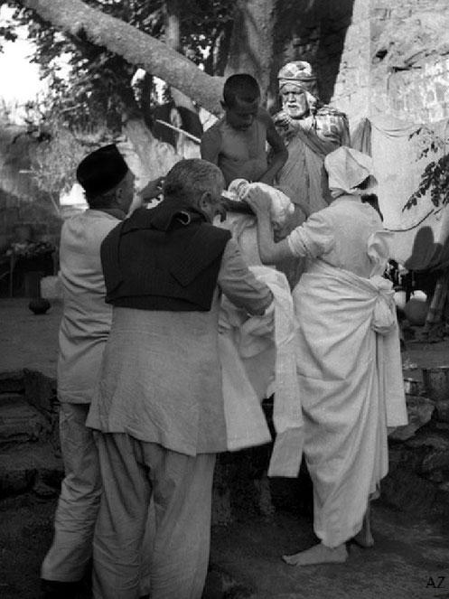 7th Nov. Meher Baba dressing the leper with new clothes, helped by Pendu & Adi K. Irani & Saint Gadge Maharaj