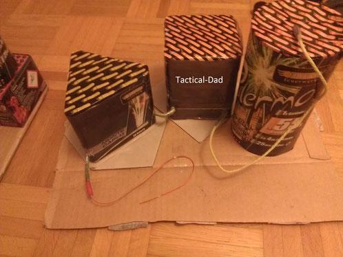 """Die Feuerwerksbatterien sind auf einer Platte festgeklebt, mit gelber Zündschnur (""""Litze"""") verbunden und mit einem Elektrozünder versehen."""