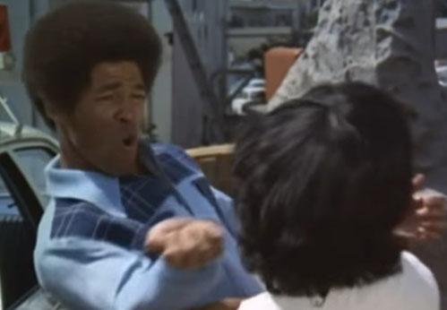 Jim Kelly in einer Filmszene, in der er seinem Gegner an den Kopf schlägt.