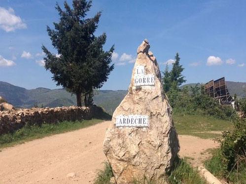 Un rocher blanc avec dessus deux pancartes indiquant l'entrée du domaine de la gorre par le gite de la gorre en location en ardeche