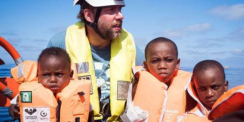 Aktivist Kai mit geretteten Kindern im Mai 2018. Foto: Chris Grodotzki