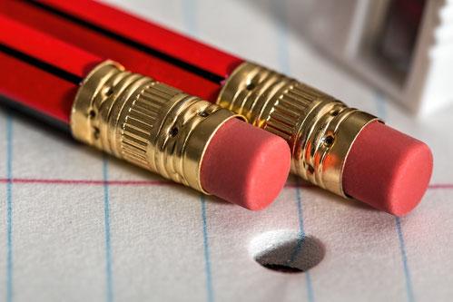Bleistifte mit Radiergummis auf Schreibblock für Korrektorat