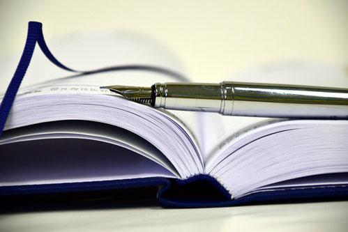 Ein Füllfederhalter auf einem Buch steht für das Lektorat