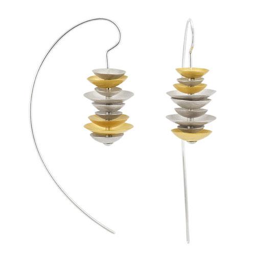 Die Ohrhänger KONKAV bestehen aus übereinander geschichteten, unterschiedlich großen Schälchen aus Silber, die teilweise goldplattiert sind. Sie sind wunderbar zart und federleicht und betören mit ihrem Farbenspiel