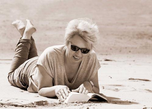 Homestory mitliegender Frau am Weserstrand, Buch lesend, trägt Sonnenbrille