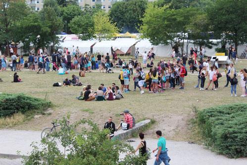 Menschen sitzen und stehen in Gruppen vor der Zeltstadt Markt Mauerpark Berlin. Foto: Helga Karl