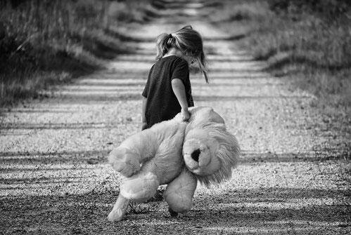 Mädchen mit großem Teddy läuft eine Landstraße entlang.