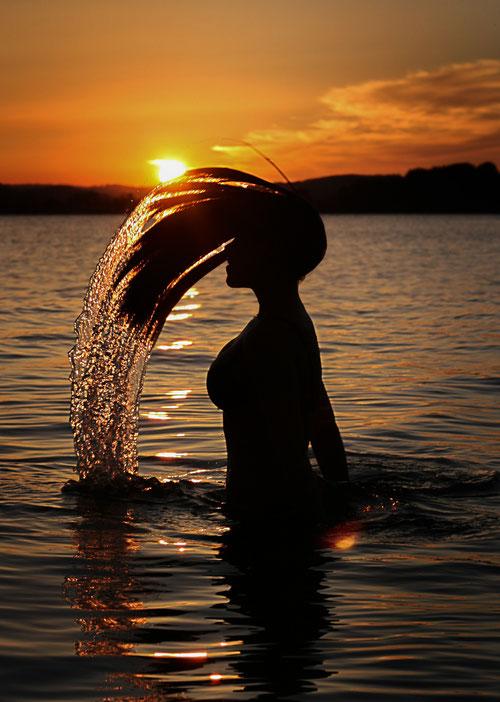 Sonnenaufgang am Obertrumer See, Seeham, Wasser, Haare, oranges Licht Morgenrot Frau Silhouette Gegenlichtaufnahme von Ralf Weichselbaumer fotografiert
