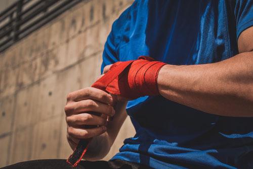 Auf dem Bild ist der Oberkörper eines Mannes zu sehen. Er trägt ein blaues T-Shirt und bandagiert seine Fäuste mit rotem Tape.