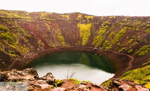 Krater mit moosbewachsener roter Vulkanerde und einem Kratersee