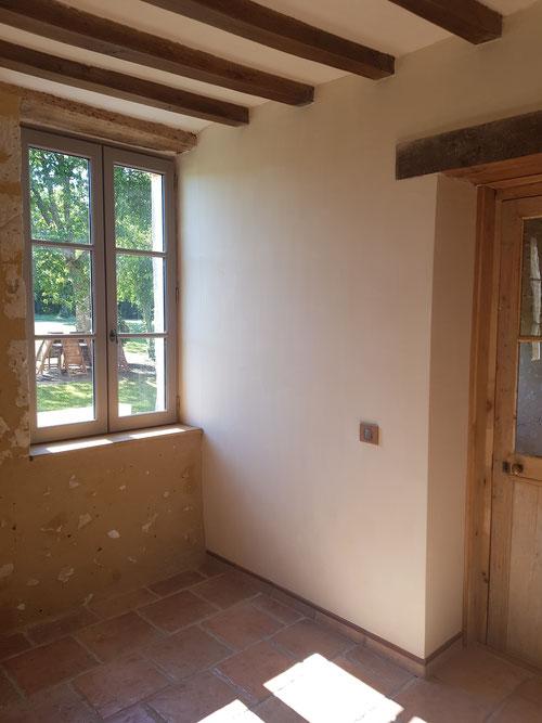 Pièce entièrement refaite : portes anciennes, remplacement fenêtres existantes par menuiseries isolantes en bois, badigeon de chaux aux murs et entres-solives, ponçage et cire poutraison,