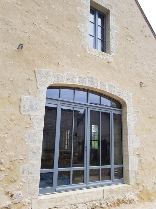 Menuiserie isolante en bois exotique deux vantaux, sur ouverture pierres de taille en anse de panier. Au dessus : fenêtre 6 carreaux égaux H165 L80