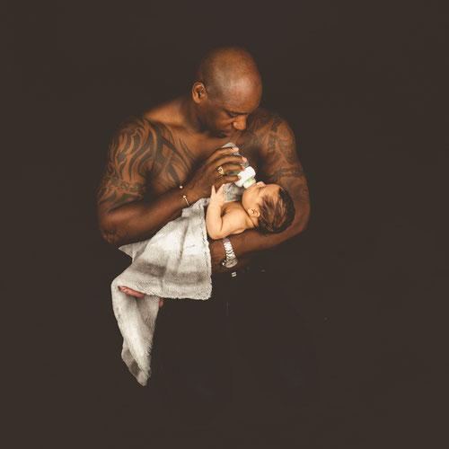 vader houdt zijn newborn in handen