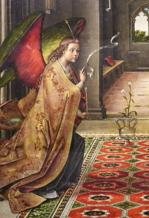 La figura del ángel vestido con capa dorada brocada sostiene un cetro o bastón de mensajero, en  en centro jarrón de cristal con tres lirios, símbolo de pureza, triple virginidad de María.(antepartum,in partu, post partum)