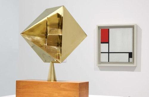En primer plano escultura de Max Bill, construcción con y en cubo,1944 y al fondo composición N.I de Mondrian.
