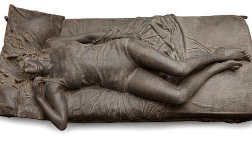 Julio López.El sueño 1976.Pizarra y piedra de Colmenar aglomeraas con resina de poliester.65x178x90cm.Colección del artista. A la cabeza dormida le falta la mitad, es una máscara,los cabellos sueltos sobrs la almohada y los pliegues de la sábana impecable
