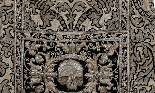 Terno funerario de las calaveras,capa pluvial, último tercio del SXVI, posterior a 1569.Terciopelo cortado de seda, anillado por trama, fondo de plata, bordado a realce en hilo y lentejuelas de plata. Sacristía del Escorial.