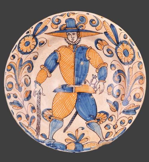 """Plato con imagen de soldado. Talavera de la Reina, Puente del Arzobispo,1650.Loza vidriada al estaño. Azul, naranja y manganeso dan título a esta serie """"tricolor"""""""