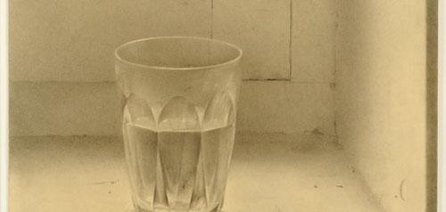 Isabel Quintanilla,Vaso1969.Lápiz sobre papel,34x25cm.Galería de Berlín,Hamburgo.Sencillez franciscana de un vaso de agua Duralex encajado en alfeizar,jamba, bisagra.La luz atraviesa el vaso y se refracta en todas sus facetas.Maestría de bodegón monocroma