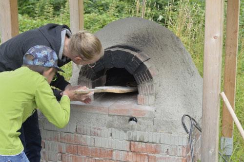 Pizza in den Lehmbackofen einschieben - Sommer-Ferienprogramm St. Georgen bei Salzburg - Camilla Harfmann