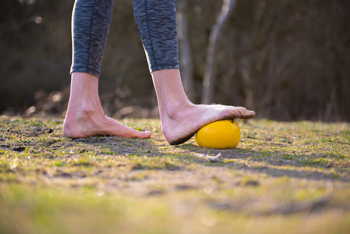 Oefening voet op gele bal in het bos, kuiten rekken.