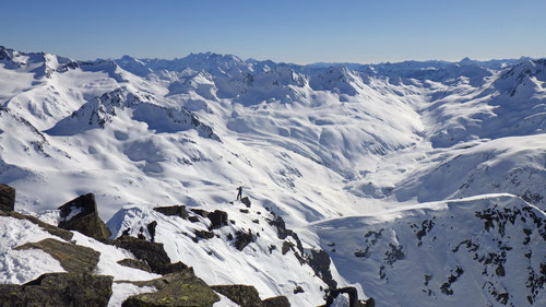 Ein Skitourenfahrer buckelt seine Ski die letzten Metern den Grat zum Rossbodenstock hoch.