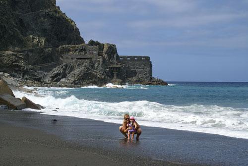 Tanja und Emilia kühlen sich die Füsse ab. Im Hintergrund das Castillo del Mar.