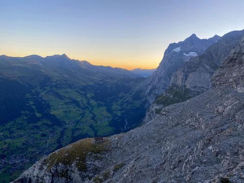 Der Tag bricht an. Im Rückspiegel die Ostegghütte und tief unten das noch schlafende Grindelwald.
