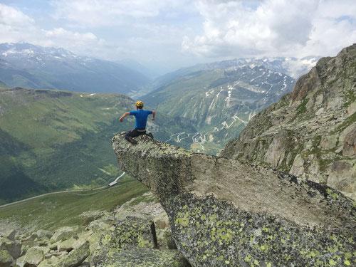 Olli reitet den Fels. Im Hintergrund ist Gletsch und die Grimselpasstrasse zu sehen.