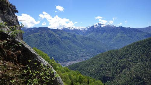 Ausblick ins Tal und auf verschneite Bergspitzen.