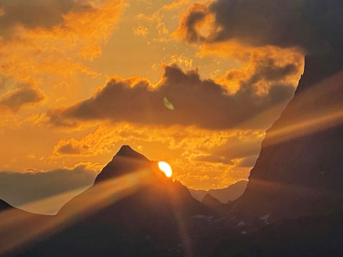 Die Sonne erscheint hinter dem Schwarz Stöckli neben der Gross Windgällen.