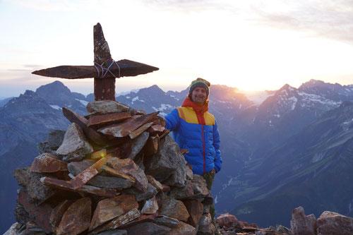 Bei Sonnenaufgang am steinernen Gipfelkreuz des Bristenstocks.