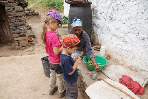 Emilia und Luca helfen beim Bohnen rüsten.
