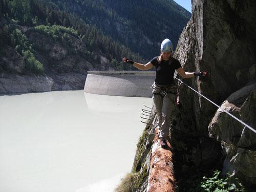 Balancieren auf dem Baumstamm. Im Hintergrund die Staumauer des Gibidum-Stausees